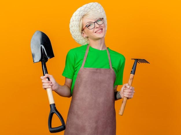 Молодая женщина-садовник с короткими волосами в фартуке и шляпе, держащая мини-грабли и лопату, смотрит в камеру, улыбаясь счастливым лицом, стоящим на оранжевом фоне