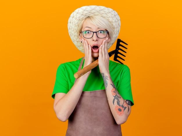 Молодая женщина-садовник с короткими волосами в фартуке и шляпе, держащая мини-грабли перед камерой, изумлена и удивлена, стоя на оранжевом фоне