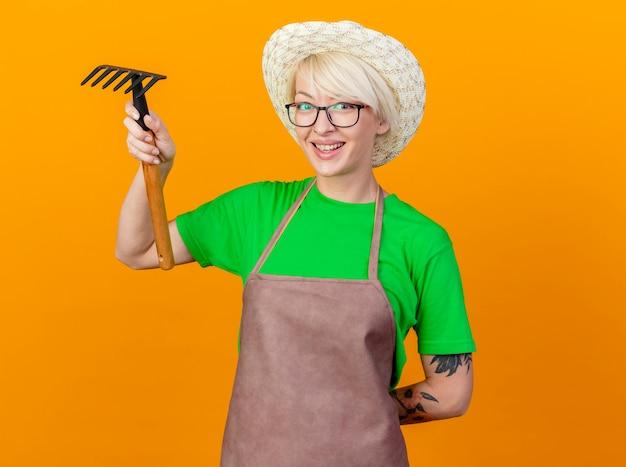 Молодая женщина-садовник с короткими волосами в фартуке и шляпе держит мини-грабли, глядя в камеру, весело улыбаясь, стоя на оранжевом фоне