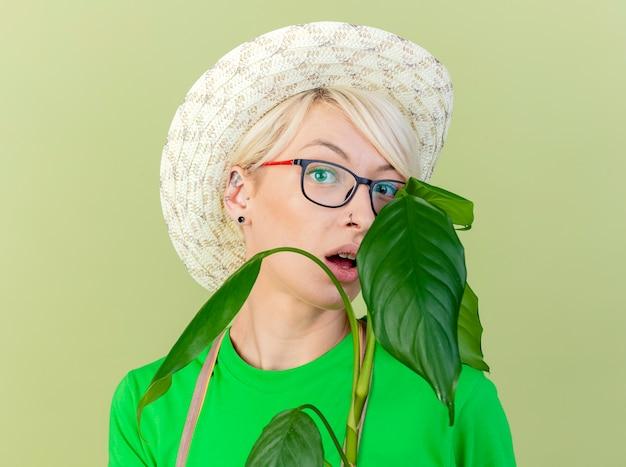 앞치마와 모자에 짧은 머리를 가진 젊은 정원사 여자는 밝은 배경 위에 서 놀란 카메라를보고 공장을 들고