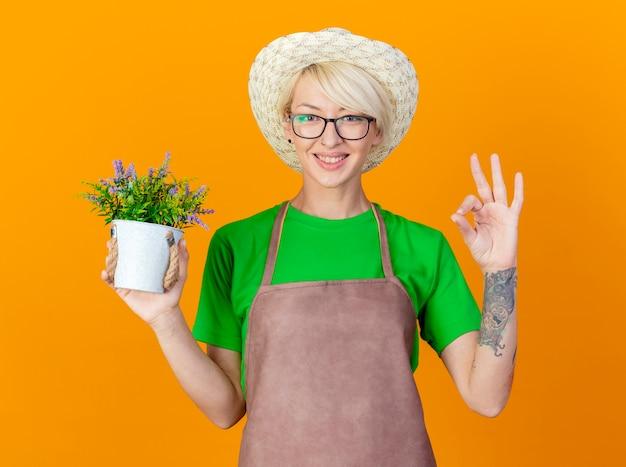 앞치마와 모자에 짧은 머리를 가진 젊은 정원사 여자 오렌지 배경 위에 서있는 확인 서명을 보여주는 행복 한 얼굴로 웃 고 카메라를보고 화분을 들고