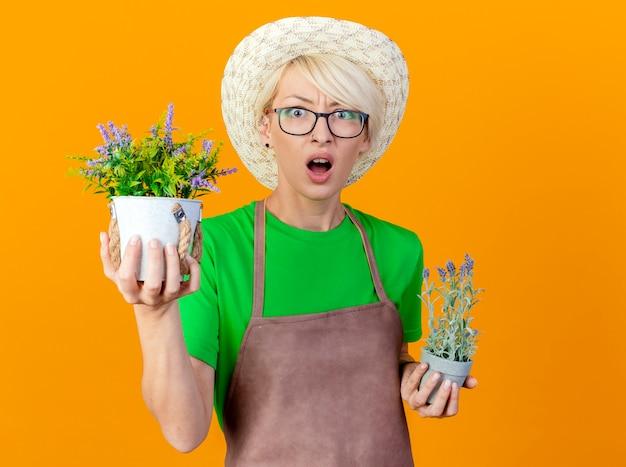 앞치마와 모자에 짧은 머리를 가진 젊은 정원사 여자는 오렌지 배경 위에 서 놀란 카메라를보고 화분을 들고 화분