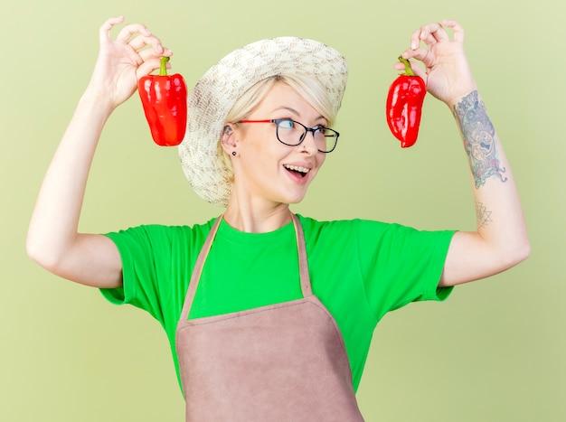 앞치마와 모자에 빨간 피망을 들고 짧은 머리를 가진 젊은 정원사 여자는 밝은 배경 위에 유쾌하게 서 웃고 재미