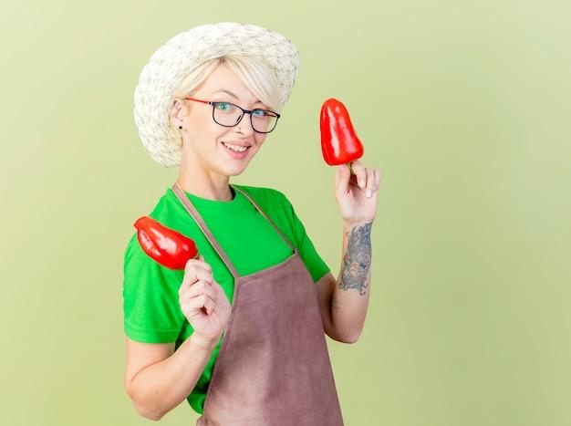 Молодая женщина-садовник с короткими волосами в фартуке и шляпе, держащая красный перец, весело улыбаясь, весело улыбаясь, стоя на светлом фоне