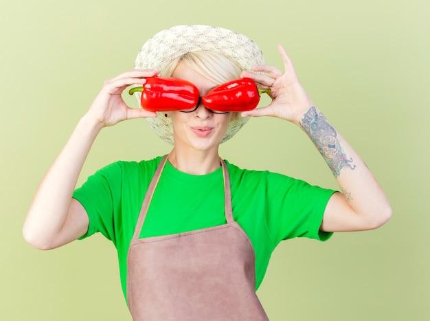 앞치마와 모자에 짧은 머리를 가진 젊은 정원사 여자는 밝은 배경 위에 서있는 웃는 그녀의 닫힌 눈 위에 빨간 피망을 들고