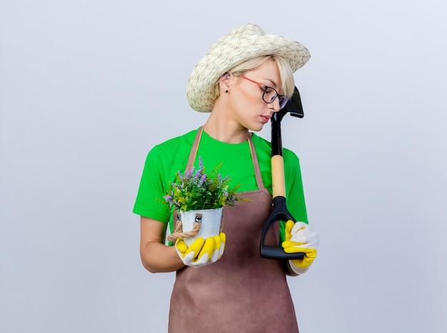 Молодая женщина-садовник с короткими волосами в фартуке и шляпе держит лопату и горшечное растение, глядя в сторону с серьезным лицом