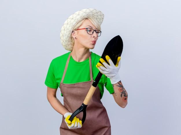 Молодая женщина-садовник с короткими волосами в фартуке и шляпе, держащая лопату, смотрит на нее, улыбаясь, собирается ее поцеловать
