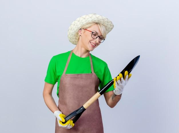 앞치마와 모자에 짧은 머리를 가진 젊은 정원사 여자는 행복한 얼굴로 웃고 그것을보고 삽을 들고