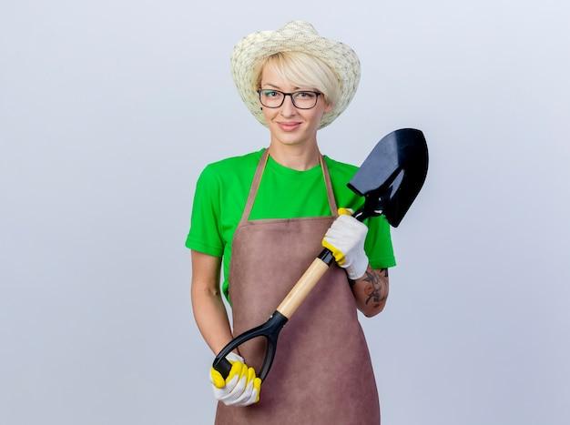 Молодая женщина-садовник с короткими волосами в фартуке и шляпе держит лопату, улыбаясь счастливой и позитивной