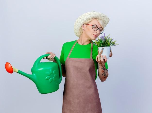 Молодая женщина-садовник с короткими волосами в фартуке и шляпе держит лейку и горшечное растение, чувствуя приятный аромат