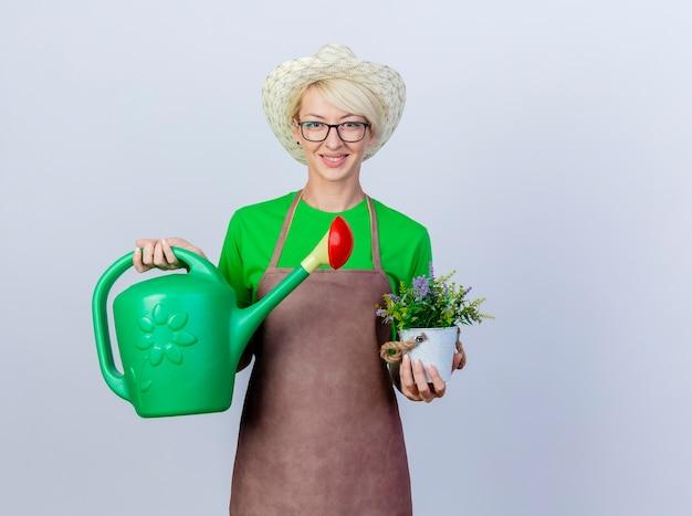 Молодая женщина-садовник с короткими волосами в фартуке и шляпе держит лейку и горшечное растение, улыбаясь счастливым лицом