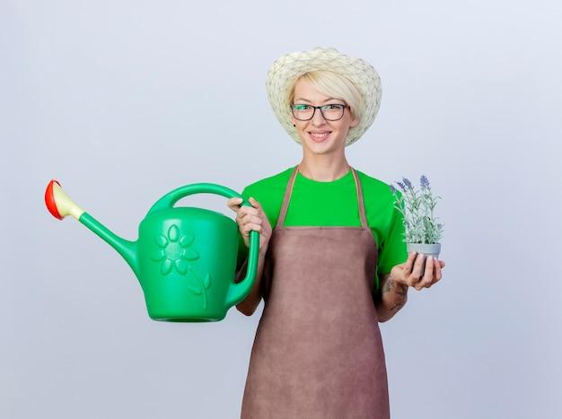 エプロンと帽子にじょうろと幸せそうな顔で微笑む鉢植えの植物を保持している短い髪の若い庭師の女性