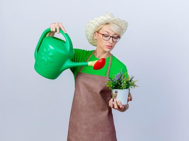 Молодая женщина-садовник с короткими волосами в фартуке и шляпе держит лейку и растение в горшке, поливает его, выглядит уверенно