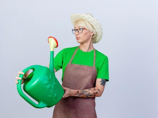 Молодая женщина-садовник с короткими волосами в фартуке и шляпе держит лейку, глядя в сторону с серьезным лицом