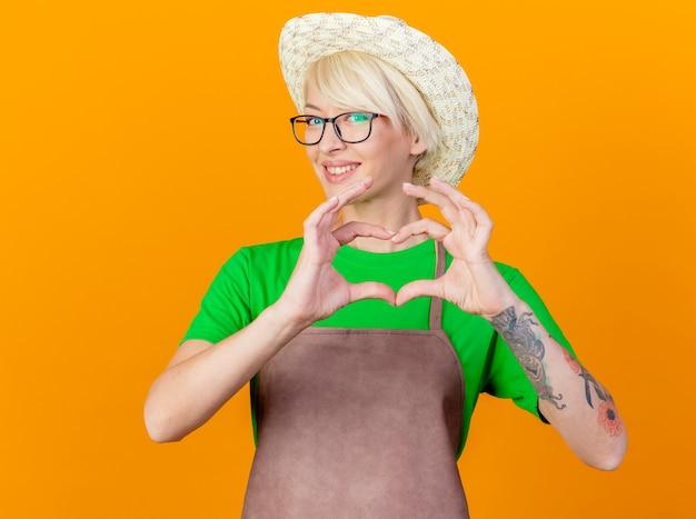 エプロンと帽子の短い髪を持つ若い庭師の女性は、オレンジ色の背景の上に立って幸せそうな顔で笑顔の指でハートジェスチャーをします