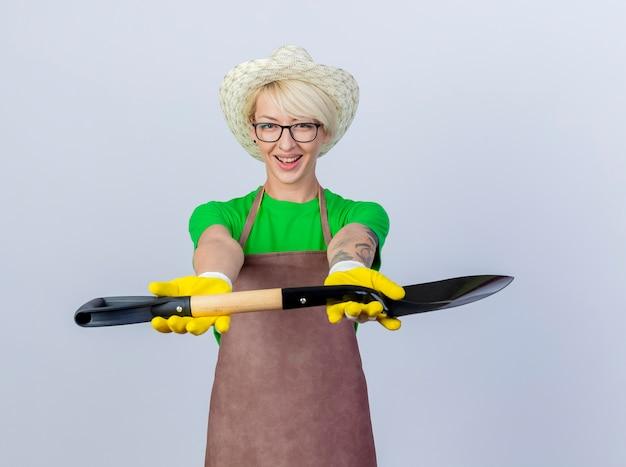 Молодая женщина-садовник с короткими волосами в фартуке и шляпе показывает лопату, улыбаясь счастливым лицом