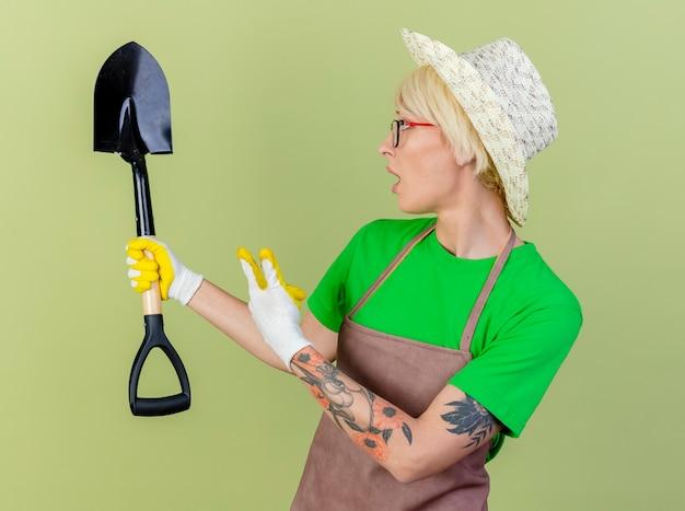 앞치마와 모자에 검지 손가락으로 가리키는 삽을 들고 고무 장갑을 끼고 짧은 머리를 가진 젊은 정원사 여자는 밝은 배경 위에 서 놀란 찾고