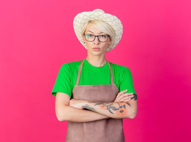 Молодая женщина-садовник с короткими волосами в фартуке и шляпе