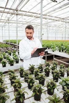 온실에서 식물을 사용하는 젊은 정원사