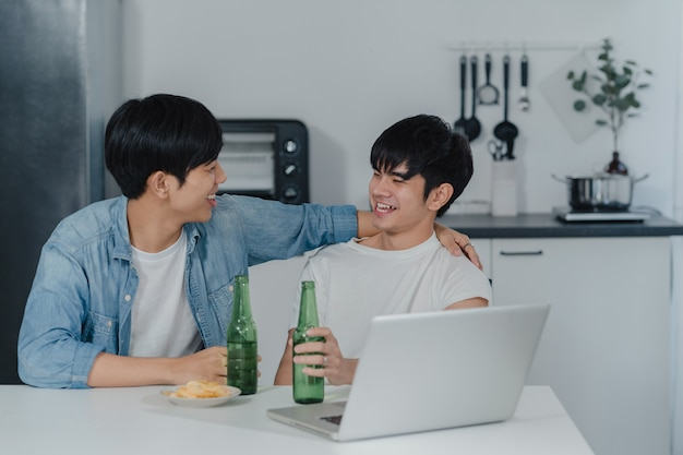 Young gay couple drink beer while using computer laptop at modern home. asian lgbtq men happy relax fun using technology play social media together while sitting table in kitchen at house .
