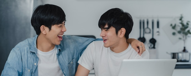 Young gay couple kissing while using computer laptop at modern home. asian lgbtq men happy relax fun using technology play social media together while sitting table in kitchen at house .