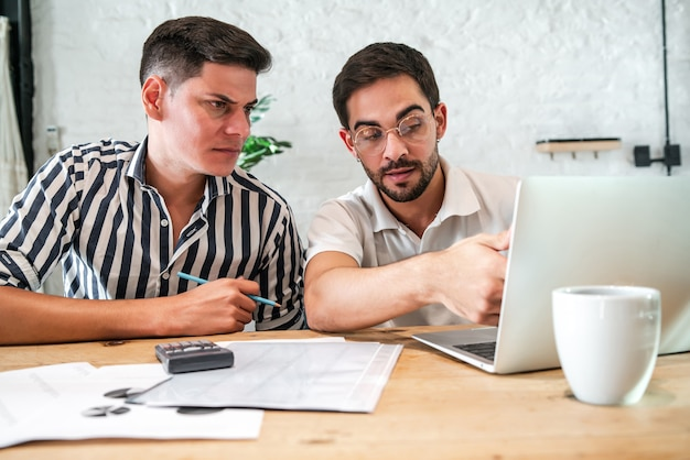 Молодая гей-пара планирует свой домашний бюджет и оплачивает счета онлайн с помощью ноутбука, оставаясь дома. концепция финансов.