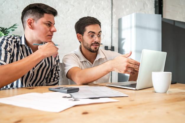 Giovane coppia gay che pianifica il budget di casa e paga le bollette online con un laptop mentre rimane a casa. concetto di finanza.