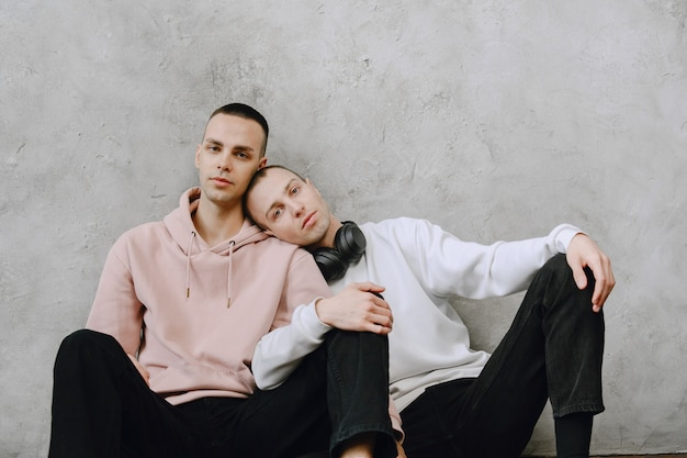 Young gay couple sitting on floor using laptop, using headphones listen to music together, hugging or embracing.