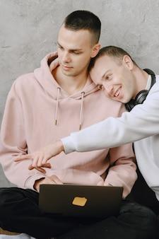 Молодая пара геев, сидя на полу с помощью ноутбука, используя наушники, вместе слушают музыку, обнимаются или обнимаются.