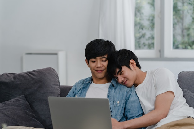 Young gay couple using computer laptop at modern home. asian lgbtq+ men happy relax fun using technology watching movie in internet together while lying sofa in living room at house .
