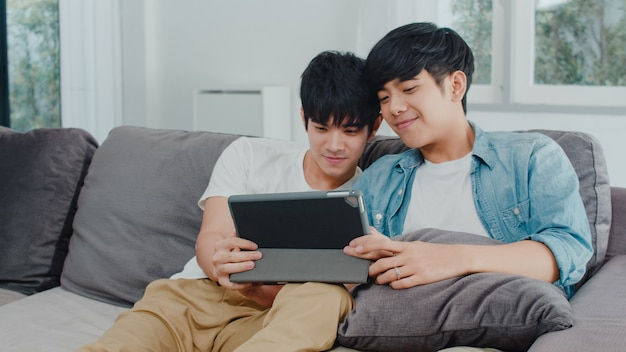 Young gay couple using tablet at home. asian lgbtq+ men happy relax fun using technology watching movie in internet together while lying sofa in living room .