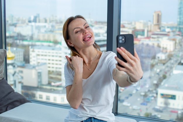 A young gay girl takes a selfie on her phone wrigging on camera while standing near a window overlooking the big city high quality photo