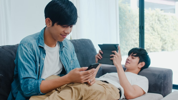 Young gay lgbtq couple using mobile phone and tablet at modern home. asian lover male happy relax laugh and fun technology play games in internet together while lying sofa in living room .