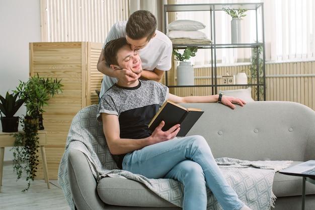 彼のboyfiendsの目を隠す若いゲイの男性、出会いに驚き。魅力的なゲイの男性は彼のボーイフレンドにキスします
