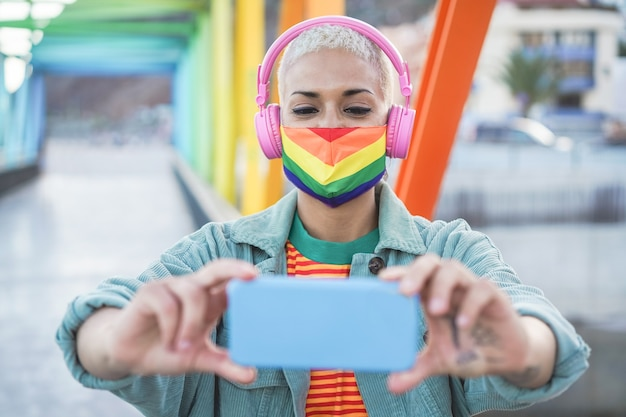 携帯電話で屋外で自分撮りをしている若いゲイの女性-虹色の旗を身に着けている技術トレンドを楽しんでいる女の子-lgbtの概念