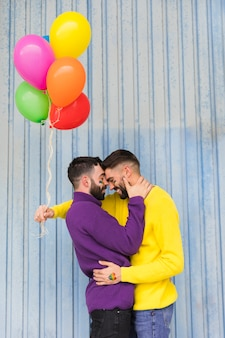 Young gays with multicolored balloons hugging on street