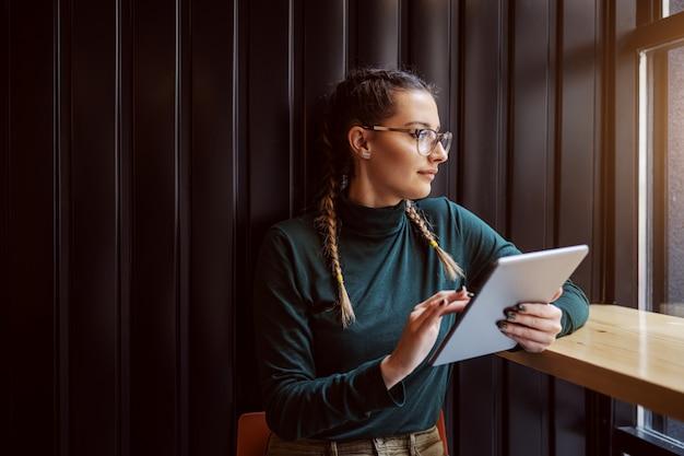 Молодая вызывающая девушка сидит в кафетерии рядом с окном, используя планшет для интернет-серфинга и смотрит в окно.