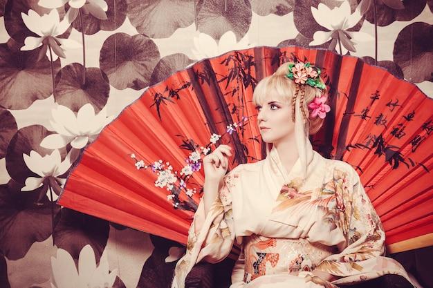 Молодая гейша в кимоно с сакурой и украшениями