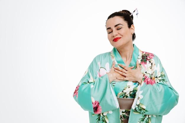 일본 전통 기모노를 입은 젊은 게이샤 여성은 행복하고 눈을 감고 기뻐하며 흰 벽 위에 서 있는 그녀의 가슴에 손을 잡고 감사함을 느낀다