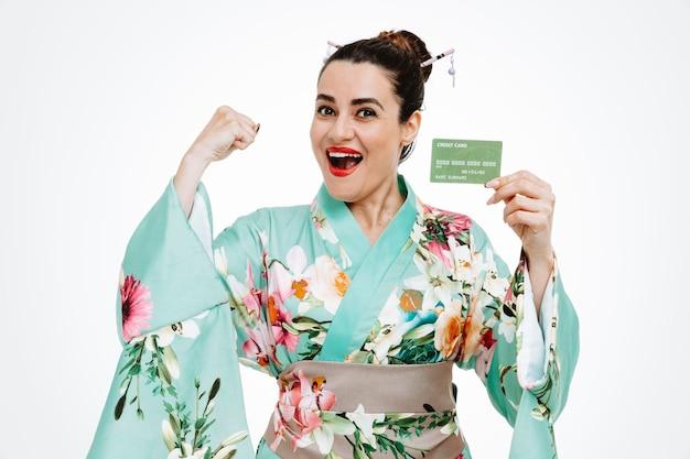 白い壁の上に立って、クレジットカードを握りこぶしを握りしめ、幸せで興奮している伝統的な日本の着物の若い芸者の女性
