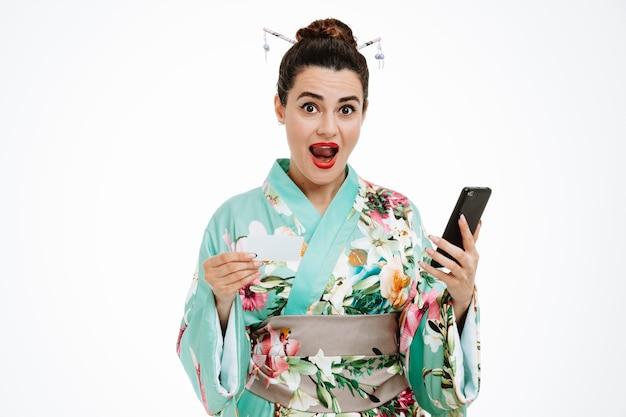スマートフォンを保持している伝統的な日本の着物の若い芸者の女性は、白い壁の上に広く立って笑顔で幸せで幸せなクレジットカードを示しています