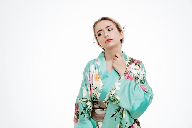 일본 전통 기모노를 입은 젊은 게이샤 여성이 흰 벽 위에 짜증을 내며 서 있는 모습