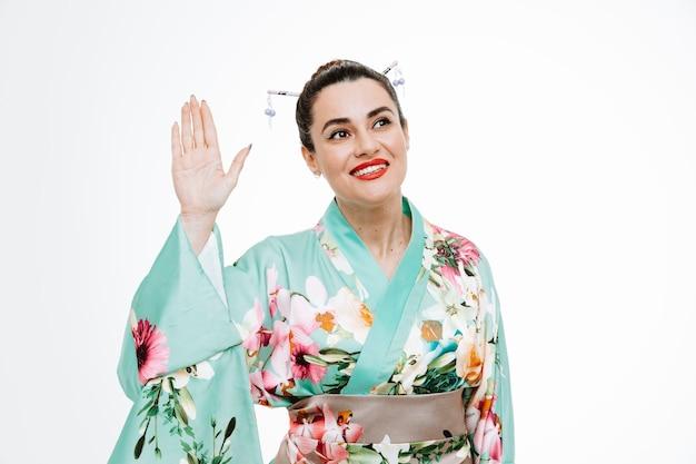 白い壁の上に立っている手で手を振って挨拶ジェスチャーを作る幸せで前向きな笑顔を脇に見ている伝統的な日本の着物の若い芸者女性