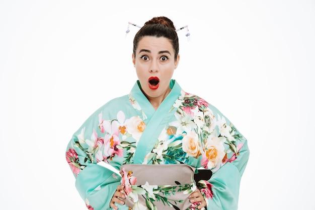 일본 전통 기모노를 입은 젊은 게이샤 여성이 입을 벌리고 눈을 크게 뜨고 흰 벽 위에 서서 놀라고 놀란다