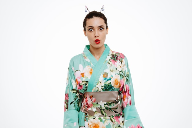 Young geisha woman in traditional japanese kimono amazed and surprised on white