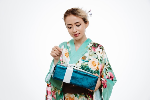 Young geisha woman in traditional japanese kimono holding present trying to open smiling cheerfully happy and intrigued standing over white wall
