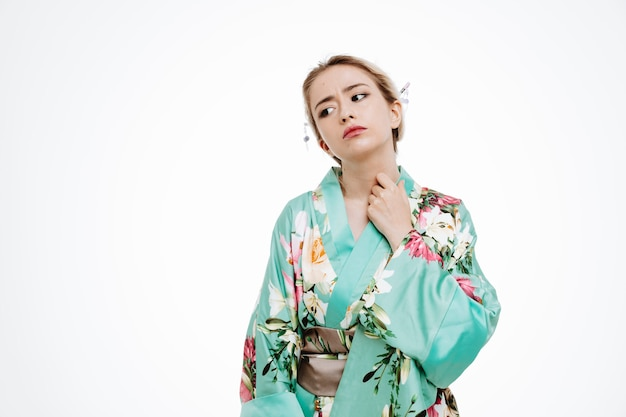 Young geisha woman in traditional japanese kimono looking annoyed and irritated standing over white wall