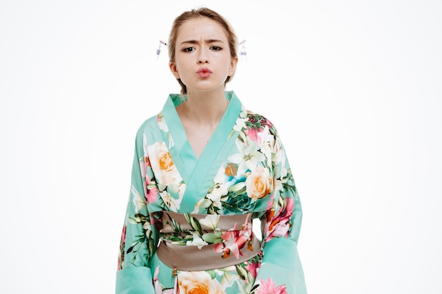 Young geisha woman in traditional japanese kimono looking at front with frowning face standing over white wall