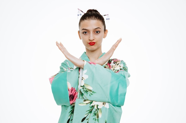 Young geisha woman in traditional japanese kimono looking at front with serious face making stop gesture crossing arms standing over white wall