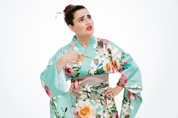 Young geisha woman in traditional japanese kimono looking up puzzled pointing with index finger to the side standing over white wall